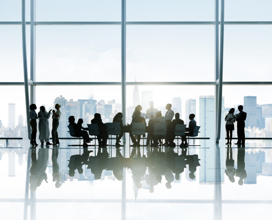 Silhouettes Of Business People Around The Conference Table With